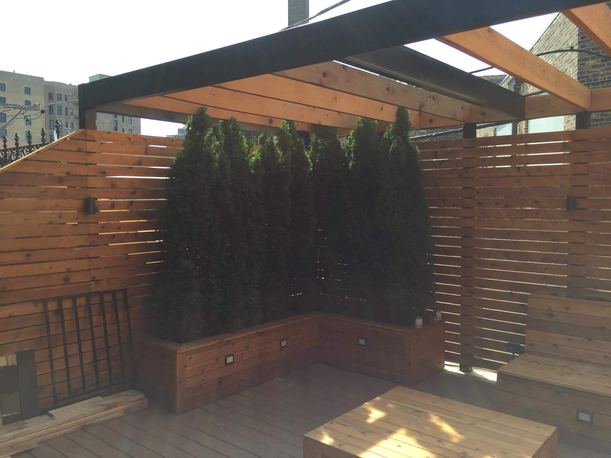 roof deck metal pergola with built in bench seating and planters lakeview chicago